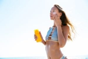 Woman applying sunscreen to face on beach.